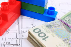 Heap of banknotes and building blocks on drawing of house. Heap of banknotes and wall of plastic colorful building blocks lying on construction drawing of house royalty free stock photography