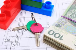 Heap of banknotes, keys and building blocks on drawing of house Stock Photos