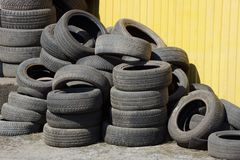 Heap of black old car tires on the street by the yellow wall royalty free stock photo