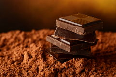 Heap of blocks of chocolate on cocoa powder Royalty Free Stock Photo