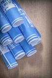 Heap of blue rolled construction drawings on wooden board Royalty Free Stock Photography
