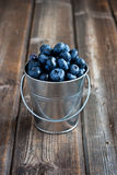 Heap of blueberry in bucket. Fresh blueberry on  old wooden table Royalty Free Stock Images