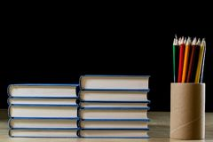 Heap of books reading on a wooden table. Beside lies and Colourful pencils. Black background. stock photography
