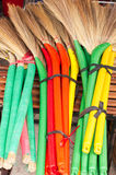 Heap of bright brooms on market Royalty Free Stock Photo