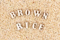 Heap of brown rice with inscription as background, healthy gluten free food concept Royalty Free Stock Photography