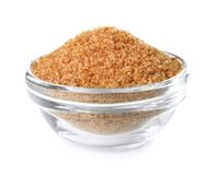 Heap of brown sugar in bowl, isolated Royalty Free Stock Images
