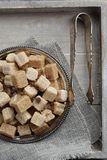 Heap of brown sugar cubes on metal plate Stock Photos