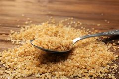 Heap of brown sugar and spoon Royalty Free Stock Image