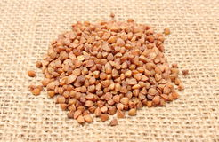 Heap of buckwheat on jute canvas Stock Photos