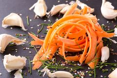 Heap of carrot shavings with few garlics around Royalty Free Stock Photos