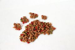 Heap of cat food set to cat footprint shape on the white floor. Cat food is food for consumption by cats. royalty free stock images
