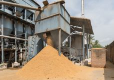 Heap of chaff falling out container at rice mill, India. Mysore, India - October 27, 2013: In Ranganathapur, the brown rice chaff falls on a heap out of a large Royalty Free Stock Photo