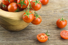 Heap of cherry tomatoes in bowl and some cut in half. On wooden surface Stock Image