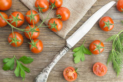 Heap of cherry tomatoes, with knife and some cut in half Stock Photos