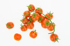 Heap of cherry tomatoes and some cut in half, on white. Background Royalty Free Stock Images