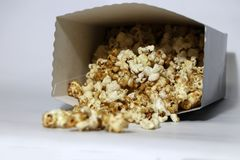 Heap of chocolate and caramel popcorn from paper box on the white floor stock image