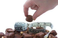 Heap of chocolates. Woman stealing a chocolate from the plate Royalty Free Stock Images