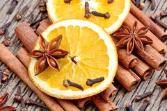 Heap of cinnamon sticks with anise clove and orange fruit Stock Photography