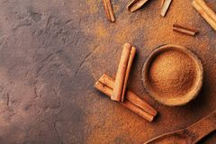 Heap of cinnamon sticks and powder on brown rustic background top view. Aromatic spices. Stock Photo