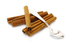 Heap of cinnamon sticks with teaspoon. On white background Royalty Free Stock Photography