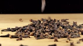 heap of cloves pouring on wooden board. spices and food ingredients. shallow depth of field