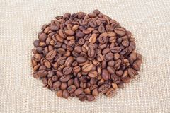 Heap of coffee beans on background of burlap. Heap of coffee beans on background of beige burlap Royalty Free Stock Images