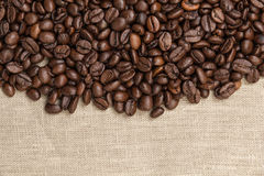 Heap of coffee beans on burlap Stock Images