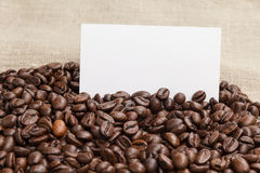 Heap of coffee beans on burlap with card Royalty Free Stock Images