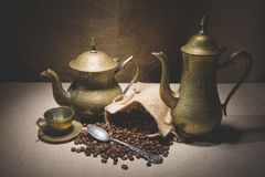 Heap of coffee beans in burlap sack with a vintage spoon and different vintage turkish coffeepots on canvas background Royalty Free Stock Images