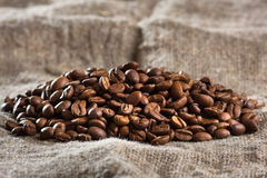 Heap of coffee beans on burlap selective focus used. Coffee beans on burlap background selective focus used Royalty Free Stock Photo