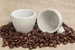 Heap of coffee beans on burlap with two cups Royalty Free Stock Photo
