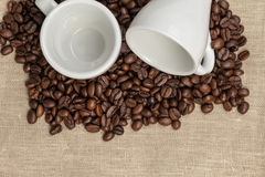 Heap of coffee beans on burlap with two cups Royalty Free Stock Photography