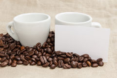 Heap of coffee beans on burlap with two cups Stock Images