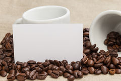 Heap of coffee beans on burlap with two cups Royalty Free Stock Image