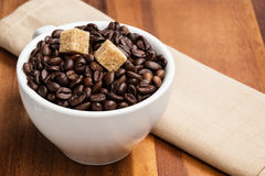 Heap of coffee beans in cup with cane-sugar. On brown wood table Stock Photo
