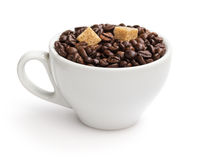 Heap of coffee beans in cup with cane-sugar. Isolated on white Royalty Free Stock Photo