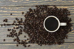 Heap of coffee beans in cup. On wood table Royalty Free Stock Photo