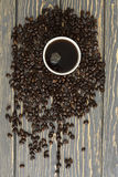 Heap of coffee beans in cup. On wood table Royalty Free Stock Images