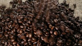 Coffee beans falling on burlap sack. Heap of coffee beans falling on brown burlap sack background stock video footage