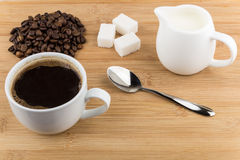 Heap of coffee beans, hot drink and jug milk Stock Photography
