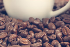 Heap of coffee beans and part of coffee cup at background vintage filtered Royalty Free Stock Image