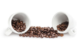 Heap of coffee beans with two cups Royalty Free Stock Images