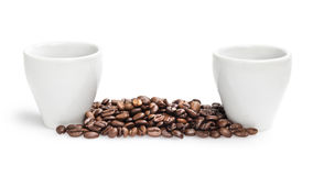 Heap of coffee beans with two cups Stock Photos