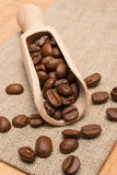 Heap of coffee beans with wooden scoop on jute burlap on table Stock Photography