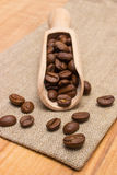 Heap of coffee beans with wooden scoop on jute canvas on table Royalty Free Stock Photo