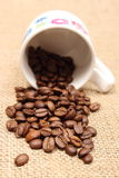 Heap of coffee grains with overturned cup Royalty Free Stock Photography