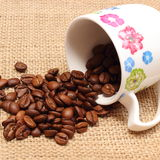 Heap of coffee grains with overturned cup Stock Photo
