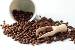 Heap of coffee grains on white board and spilled cup Stock Images