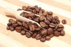 Heap of coffee on wooden spoon. Wooden background Stock Image
