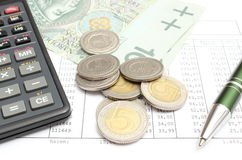 Heap of coins, paper money, calculator and pen on spreadsheet Royalty Free Stock Image